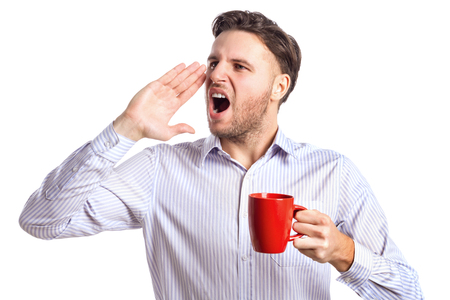 far away: Handsome Businessman Holding Red Cup And Screaming At Something Far Away Isolated On White Background Stock Photo
