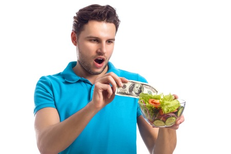 stash: Handsome Man Gets A Hundred Dollars Of Salad Isolated On White Background. Healthy Eating Theme
