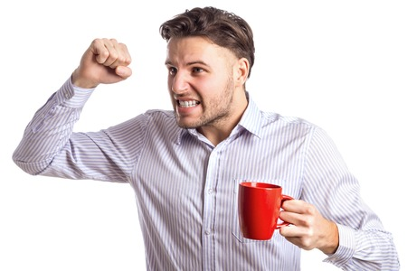 brandishing: Handsome Angry Businessman Brandishing His Fist Holding Red Cup And Screaming At Something Far Away Isolated On White Background Stock Photo