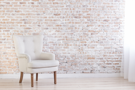 feature wall: White Armchair On Brick Wall Background Near Window