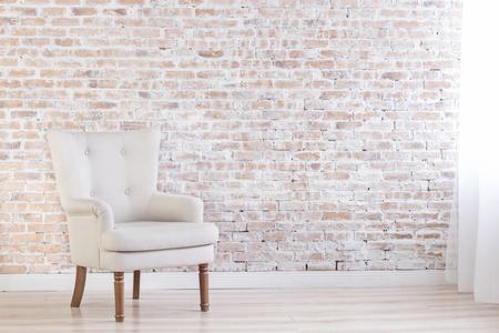 antique furniture: White Armchair On Brick Wall Background Near Window