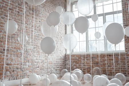 Globos blancos y transparentes sobre fondo de pared de ladrillo Foto de archivo