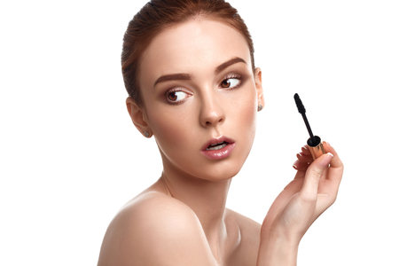 makeup a brush: Beautiful Young Woman With Makeup Brush Applying Black Mascara On Eyelashes Isolated On White Background. Skin Care Theme Stock Photo