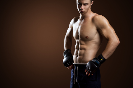 mixed martial arts: Mixed Martial Arts Fighter Posing On Brown Background Stock Photo