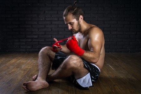 mixed martial arts: Mixed Martial Arts Fighter Preparing Red Bandages For Training