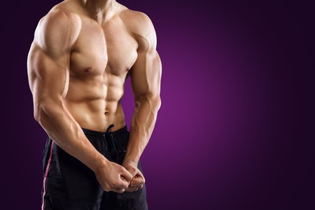 Muscular Handsome Fitness Man Demonstrates His Abdominal Muscles On Purple Background Stock Photo