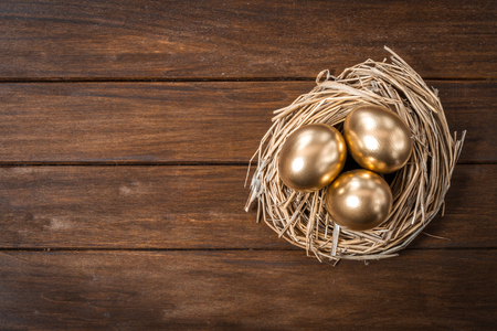 Three Golden Eggs In A Nest On Wooden Table