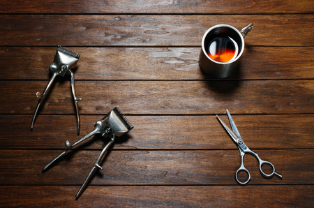 hair clippers: Two Old Vintage Manual Metal Hair Clippers, Scissors And Cup On Wooden Table Stock Photo