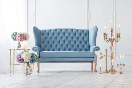 Schöne Provance Wohnzimmer mit blauen Sofa in der Nähe Tisch mit Blumen und Kerzen