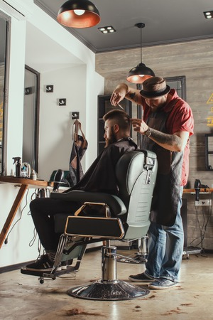 barber scissors: Serious Young Bearded Man Getting Haircut By Barber. Barbershop Theme