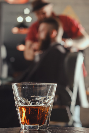 Glass Of Whiskey On A Background Of Man Getting Haircut By Barber While Sitting In Chair At Barbershop. Barbershop Theme Standard-Bild