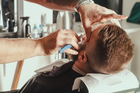 barbershop: Young Bearded Man Getting Beard Haircut With A Straight Razor By Barber. Barbershop Theme Stock Photo