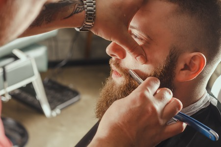 straight razor: Young Bearded Man Getting Beard Haircut With A Straight Razor By Barber. Barbershop Theme Stock Photo