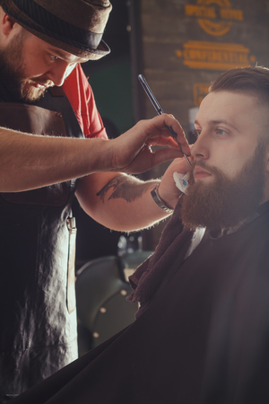 haircut: Young Bearded Man Getting Beard Haircut With A Straight Razor By Barber. Barbershop Theme Stock Photo