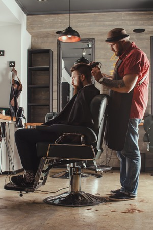 barbershop: Serious Young Bearded Man Getting Haircut By Barber. Barbershop Theme