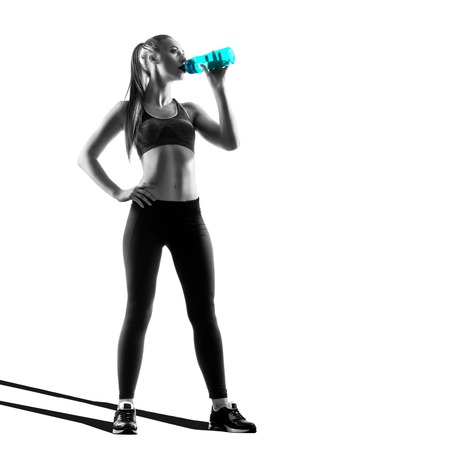 sports clothing: Young Fitness Woman Silhouette Drinking Water Of Blue Bottle Isolated On White Background. Fitness Theme