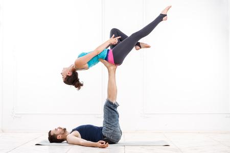 excercise: Young Beautiful Man And Woman Practicing Acroyoga Doing Excercise In White Interior