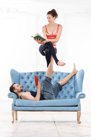 position d amour: Young Beautiful Man And Woman Practicing Acroyoga On Blue Sofa Doing Excercise And Reading Books In White Interior