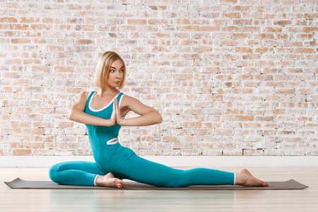 Young Beautiful Woman Practicing Yoga Doing Excercise On Brick Wall Ball Background Stock Photo