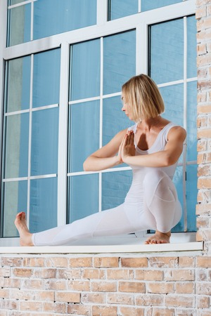 excercise: Young Beautiful Woman Practicing Yoga Doing Excercise On A Windowsill