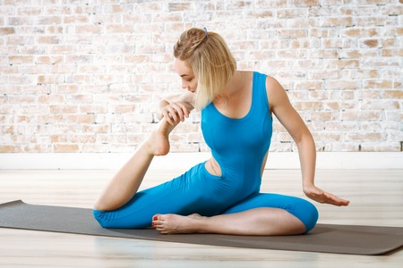excercise: Young Beautiful Woman Practicing Yoga Doing Excercise On Brick Wall Ball Background Stock Photo