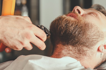 barbershop: Serious Bearded Man Getting Beard Haircut By Barber While Sitting In Chair At Barbershop. Barbershop Theme