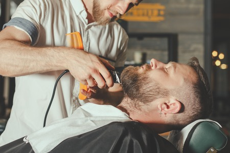 barbershop: Serious Bearded Man Getting Beard Haircut By Barber While Sitting In Chair At Barbershop. Barbershop Theme