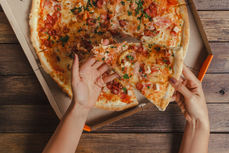 pizza cutter: Female Hands Taking Slice Of Pizza On Wooden Table Stock Photo