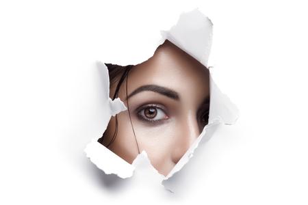 화이트 통해 찾고 갈색 눈을 가진 여자 찢어진 된 종이 구멍 스톡 콘텐츠 - 67614010
