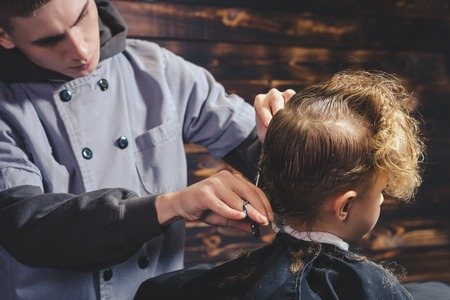 deadpan: Little Boy Getting Haircut By Barber While Sitting In Chair At Barbershop. Barbershop Theme
