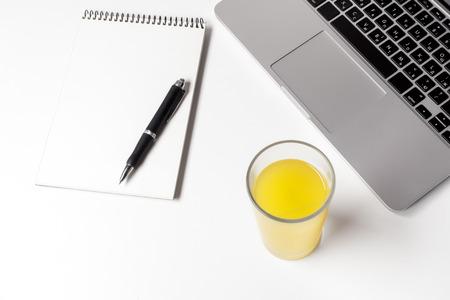 Glas mit Saft und Notizbuch mit Stift in der Nähe von Laptop