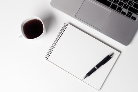 Tasse mit Kaffee und Notebook mit Stift in der Nähe von Laptop