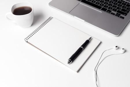 Tasse mit Kaffee, Notizbuch mit Stift und Kopfhörer in der Nähe von Laptop