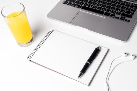 Glas mit Saft, Notizbuch mit Stift und Kopfhörer nahe Laptop