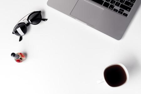 Tasse mit Kaffee, Sonnenbrille und Nagellack in der Nähe von Laptop