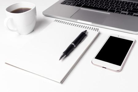 Cup mit Kaffee, Notizbuch mit Stift und Smartphone in der Nähe von Laptop Standard-Bild