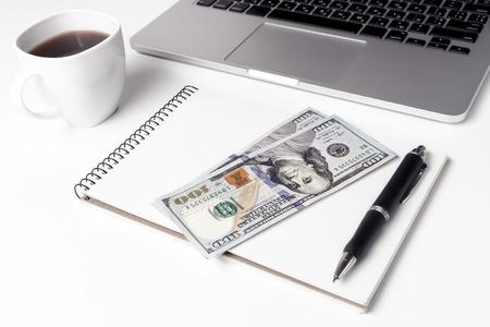 Tasse mit Kaffee und Notebook, auf der zweihundert Dollar Ne liegen Standard-Bild