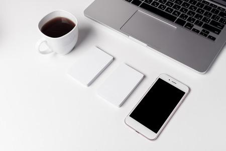 Schale mit Kaffee, Visitenkarten und Smartphone in der Nähe von Laptop Standard-Bild