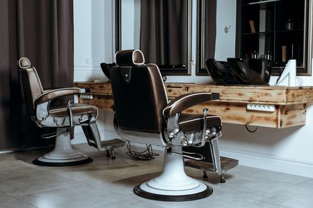 Stilvolle Vintage Barber Stühle im hölzernen Innenraum. Barbershop-Thema