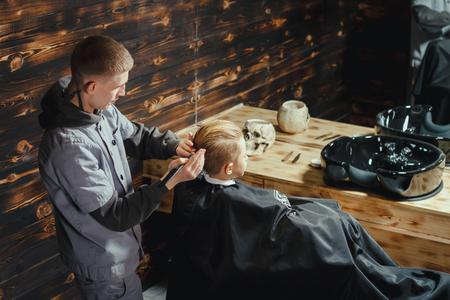 Little Boy, der Haarschnitt von Barber Während im Stuhl zu sitzen Friseursalon. Friseursalon-Theme Standard-Bild