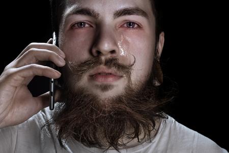 Crying Bearded Man Holding A Smartphone Near Your Ear Standard-Bild