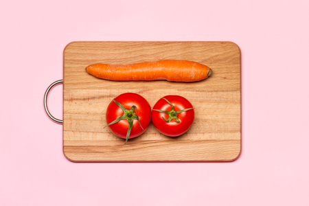 Healthy Eating. Two Fresh Tomato Near One Carrot On A Wooden Chopping Board Stock Photo