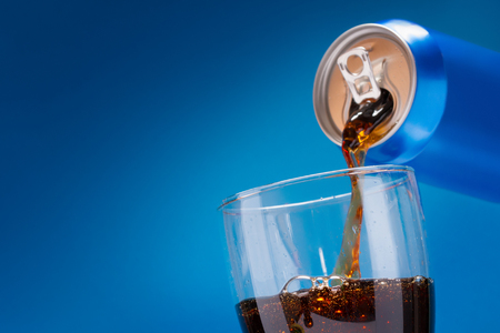 Pouring Refreshing Sugary Soft Drink From A Blue Drink Can Into A Glass On A Blue Background