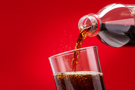 Pouring Refreshing Sugary Soft Drink From A Plastic Bottle Into A Glass On A Red Background 免版税图像