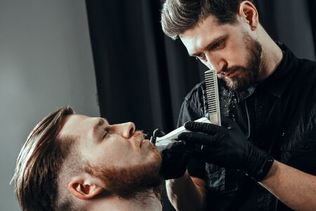 BARBERSHOP THEME. BEARDED SERIOUS BARBER IN BLACK RUBBER GLOVES IS TRIMMING THE BEARD OF HIS YOUNG HANDSOME CLIENT WITH CLOSED EYES. HE IS USING A HAIR CLIPPER