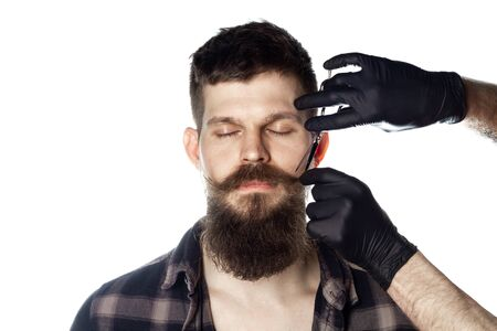 Man With Long Beard And Closed Eyes In Plaid Shirt Isolated On White Background. Barbershop Theme. The Hand Of The Barber In Black Gloves Hold A Scissors Near The Face Banque d'images