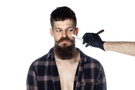 Handsome Man With Long Beard In Plaid Shirt Isolated On White Background. Barbershop Theme. The Hands Of The Barber In Black Gloves Hold A Razor Near The Face Of A Man