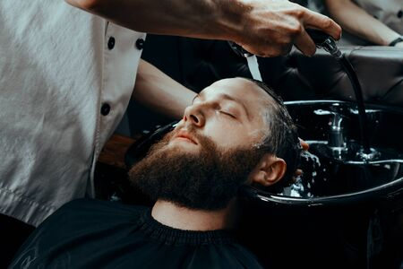 BARBERSHOP THEME. BARBER WASHING CLIENTS HAIR IN BARBER SHOP. BEARDED MAN SITTING IN BARBER CHAIR