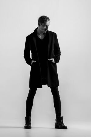Handsome Fashion Man In Black Coat Posing On White Background. Model Test