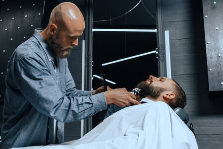 BARBERSHOP THEME. BALD BEARDED BARBER IS TRIMMING THE BEARD OF HIS YOUNG HANDSOME CLIENT. HE IS USING A HAIR CLIPPER